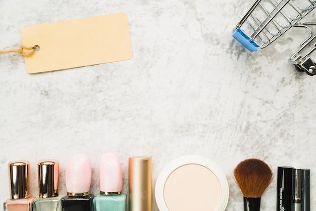 Carrinho de compras com pequena etiqueta perto de linha de cosméticos