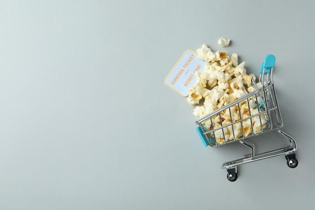 Carrinho de compras com pipoca e ingresso em fundo cinza claro.
