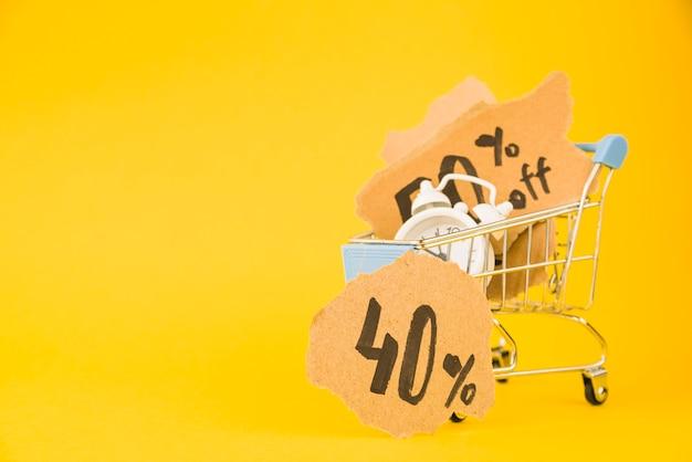 Carrinho de compras com pouco despertador e pedaços de venda de papel