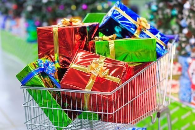 Carrinho de compras com presentes no fundo do supermercado