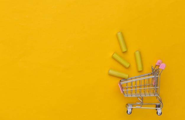 Carrinho de compras com quatro pilhas aa amarelas em fundo amarelo. vista do topo