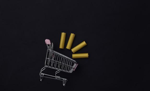 Carrinho de compras com quatro pilhas aa amarelas em fundo preto. vista do topo