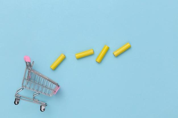 Carrinho de compras com quatro pilhas aa amarelas sobre fundo azul. vista do topo