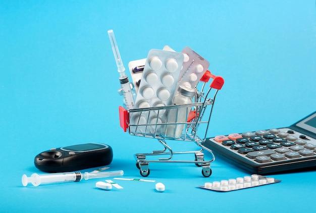 Carrinho de compras com remédios, seringas de insulina para diabetes e calculadora.