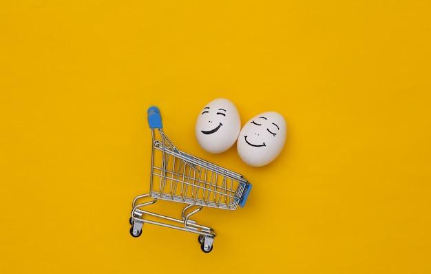 Carrinho de compras com rostos de ovos felizes em fundo amarelo