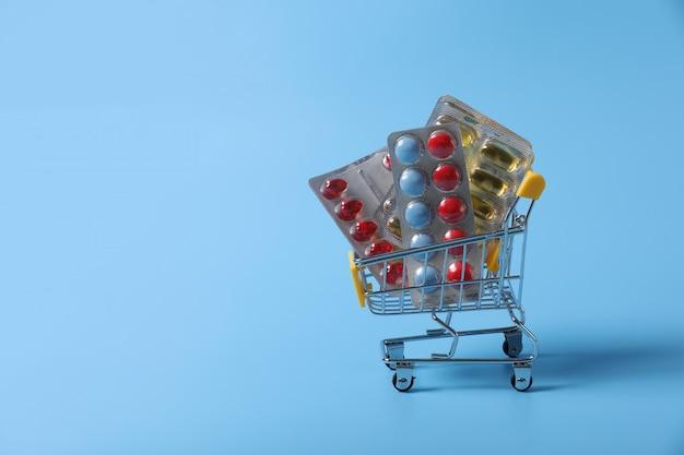 Carrinho de compras com suprimentos médicos isolado na parede azul. remédio na cesta. venda de medicamentos.