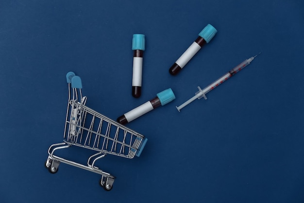 Carrinho de compras com tubos de ensaio médicos, seringa em um fundo azul clássico. vista do topo
