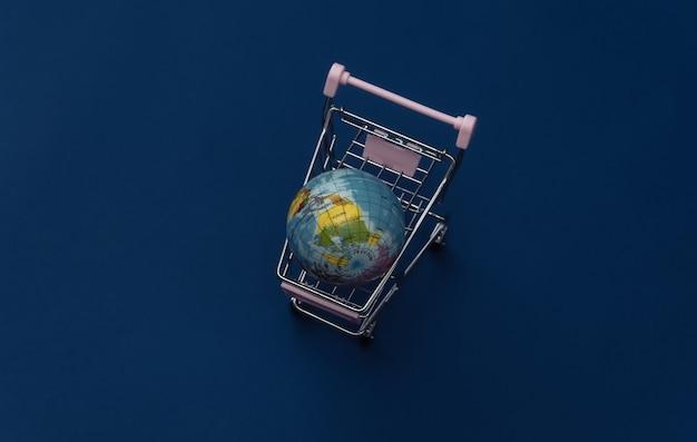 Carrinho de compras com um globo sobre fundo azul clássico. supermercado global. color 2020.