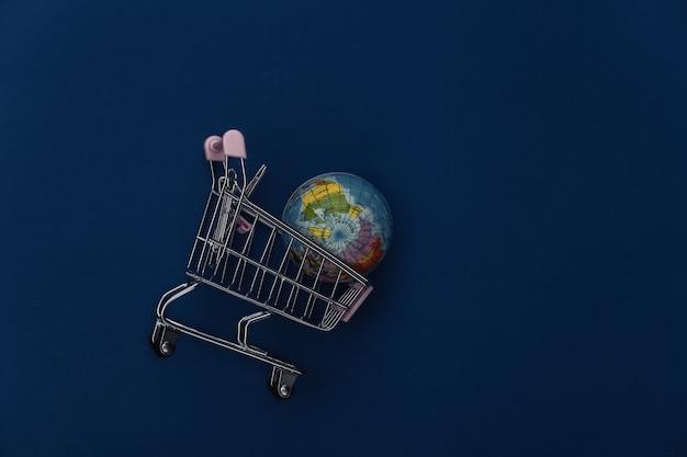 Carrinho de compras com um globo sobre fundo azul clássico. supermercado global. cor 2020. vista superior.