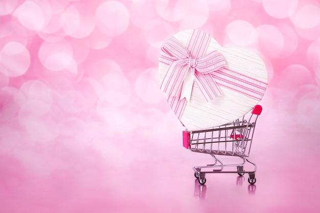 Carrinho de compras com um grande presente com forma de coração em rosa com fundo bokeh.