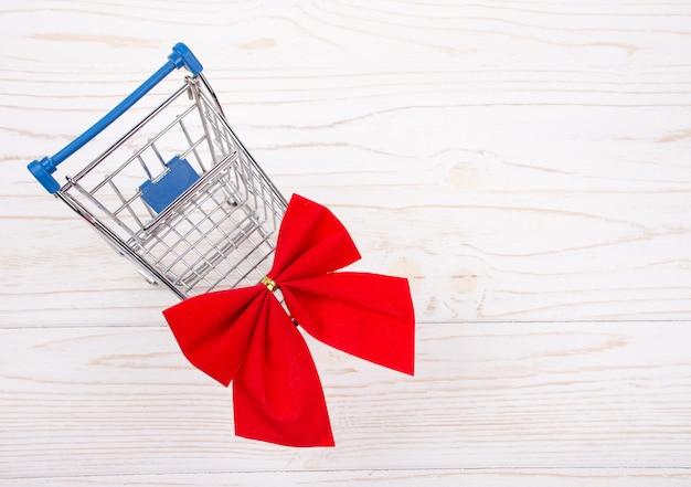 Carrinho de compras com um laço vermelho