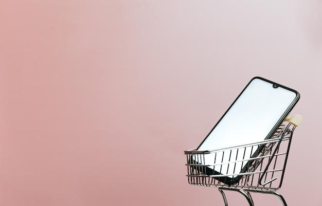 Carrinho de compras com um telefone celular em branco sobre um fundo rosa pastel, comércio eletrônico, compra online, comércio online, plano de fundo, tecnologia, dia de compras, sexta-feira negra e rede, espaço de cópia, simulação