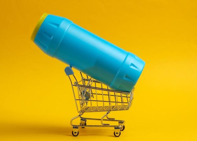 Carrinho de compras com uma garrafa plástica branca de detergente para o banheiro e o toalete em fundo amarelo.