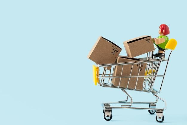 Carrinho de compras de brinquedo com caixas em fundo azul