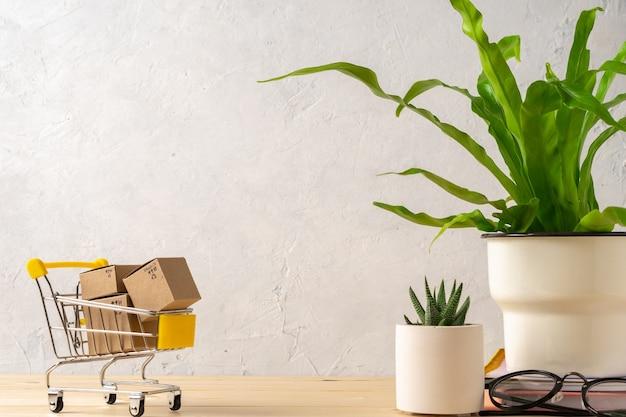 Carrinho de compras de brinquedo com caixas na mesa de madeira com planta