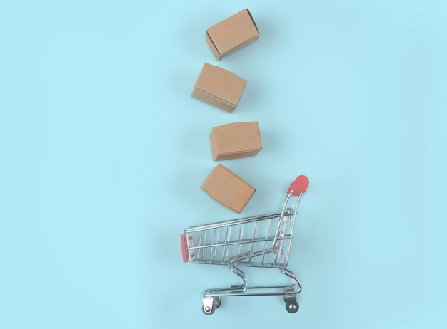 Carrinho de compras de brinquedo com conceito de compras e entrega de caixas. tendência da sociedade de consumo