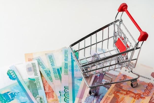 Carrinho de compras de brinquedo com dinheiro em rublos russos. salário e poder de compra