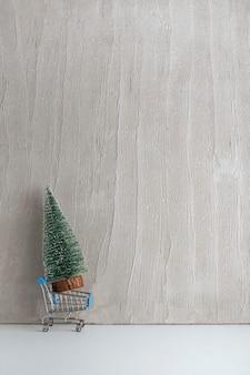 Carrinho de compras de brinquedo e pequena árvore de natal artificial. comprando árvore de natal. copie o espaço. quadro vertical.
