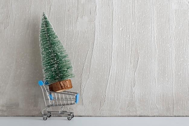 Carrinho de compras de brinquedo e pequena árvore de natal artificial. comprando árvore de natal. copie o espaço