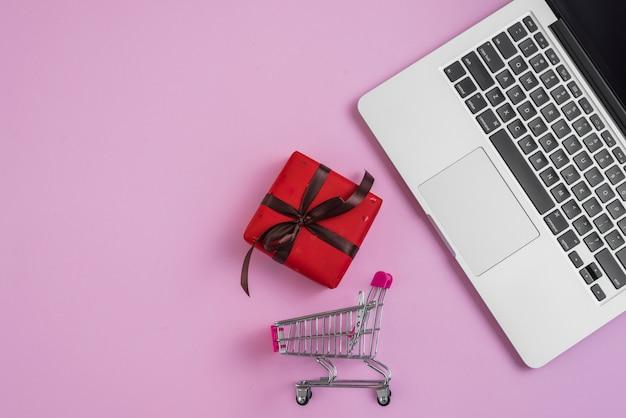 Carrinho de compras de brinquedo e presente perto de teclado de laptop