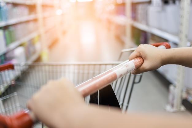Carrinho de compras de mão de mulher no supermercado