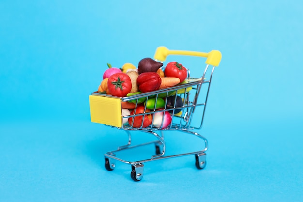 Carrinho de compras de metal com frutas e vegetais em um fundo azul
