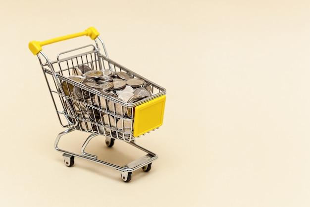 Carrinho de compras de metal com moedas de metal em um fundo bege conceito de dinheiro