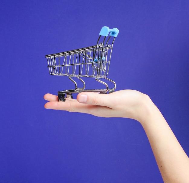 Carrinho de compras de mini brinquedo de metal na mão feminina sobre fundo roxo. conceito de entrega