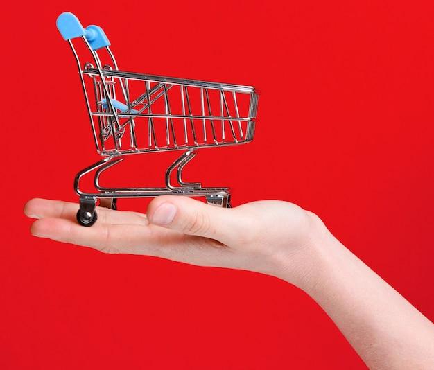 Carrinho de compras de mini brinquedo de metal na mão feminina sobre fundo vermelho. conceito de entrega