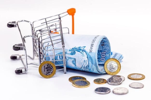 Carrinho de compras de supermercado criado com notas de cem dólares e moedas espalhadas pelo chão, conceito de crise financeira