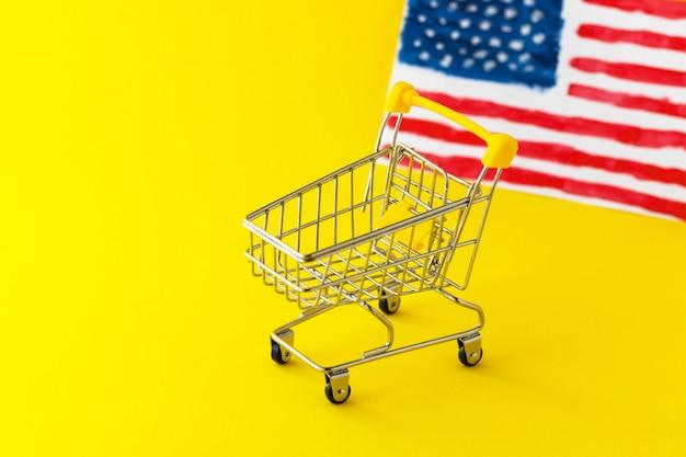 Carrinho de compras de supermercado mini e abstrato mão desenhada bandeira americana em fundo amarelo