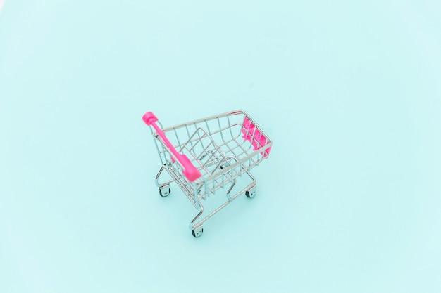 Carrinho de compras de supermercado pequeno carrinho de compras de brinquedo com rodas isoladas no espaço na moda colorido pastel azul copie o espaço. venda comprar shopping mercado conceito de consumidor de loja.
