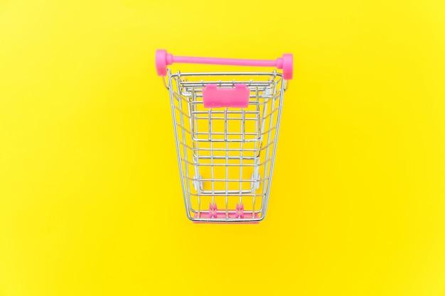 Carrinho de compras de supermercado pequeno para compras de brinquedo com rodas isoladas em fundo amarelo moda moderno colorido moda. venda comprar shopping mercado conceito de consumidor de loja. copie o espaço.