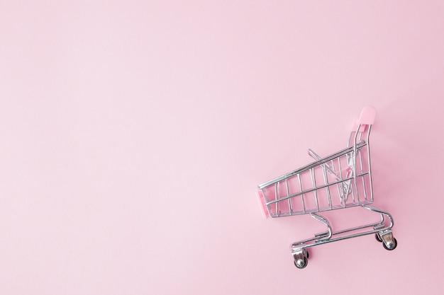 Carrinho de compras de supermercado pequeno supermercado para comprar brinquedos com rodas e elementos plásticos rosa sobre fundo de papel de cor pastel rosa colocar fundo. conceito de compras. copie o espaço para propaganda