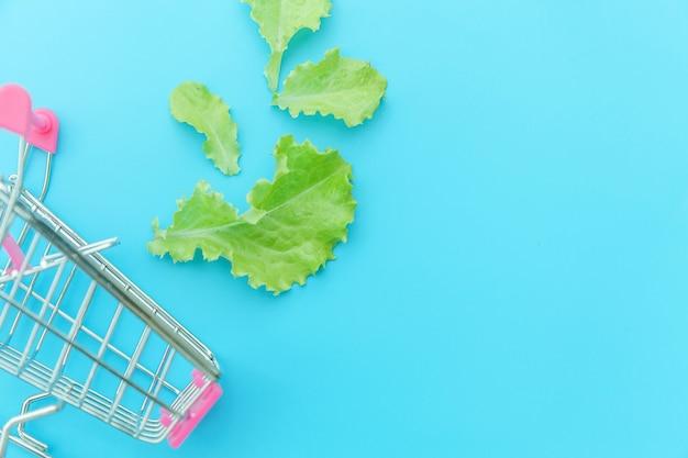 Carrinho de compras de supermercado pequeno supermercado para fazer compras com folhas de alface verde, isoladas no fundo azul