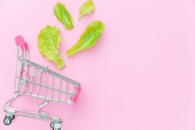 Carrinho de compras de supermercado pequeno supermercado para fazer compras com folhas de alface verde, isoladas no fundo rosa
