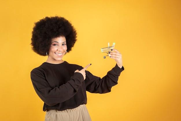 Carrinho de compras de uma mulher bonita e afro, compras online