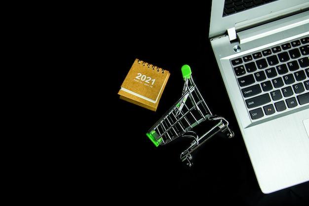 Carrinho de compras de vista superior e calendário 2021 perto de um laptop com fundo preto.