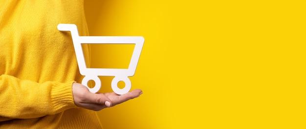 Carrinho de compras disponível sobre fundo amarelo, imagem panorâmica, conceito de compra online