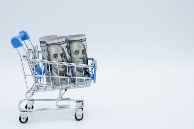 Carrinho de compras do close up com a cédula do dólar americano no fundo branco.