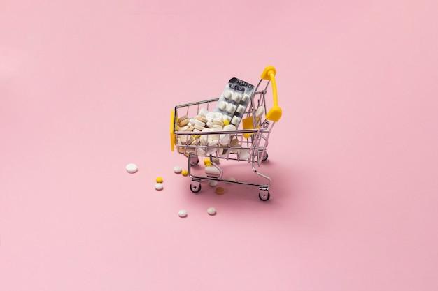 Carrinho de compras do supermercado cheio de comprimidos e drogas em um fundo rosa. compras de medicamentos, compra na internet.