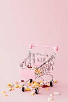 Carrinho de compras do supermercado cheio de comprimidos e drogas em uma parede rosa. compras de medicamentos, compra na internet. vista plana, vista superior