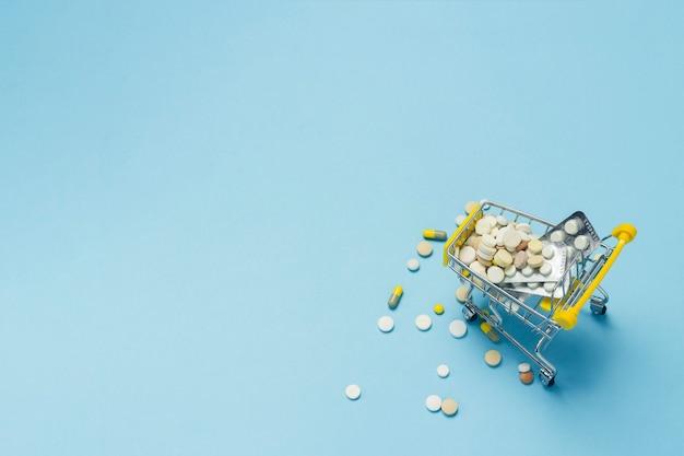 Carrinho de compras do supermercado cheio de pílulas sobre um fundo azul. compras de medicamentos, compra na internet. vista plana leiga, superior.
