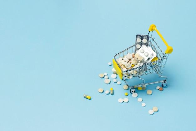 Carrinho de compras do supermercado cheio de pílulas sobre um fundo azul.