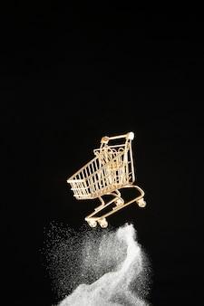 Carrinho de compras dourado com glitter branco sobre fundo preto