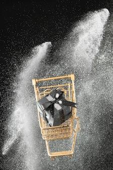 Carrinho de compras dourado em glitter branco com presente