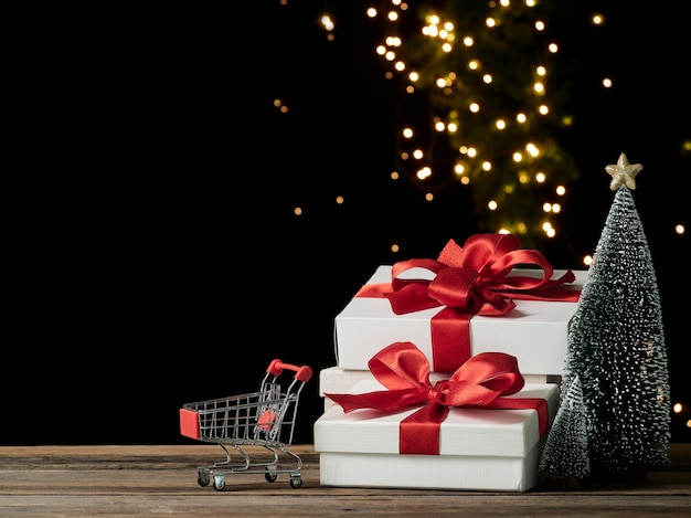 Carrinho de compras e caixas de presente de natal na mesa de madeira, espaço para texto