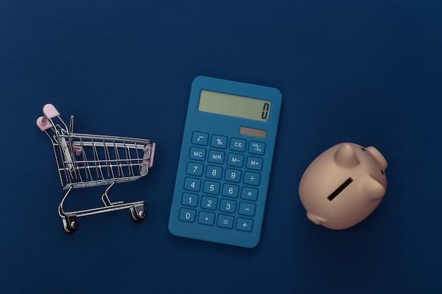 Carrinho de compras e calculadora, cofrinho em fundo azul clássico. custos de supermercado. cor 2020. vista superior.