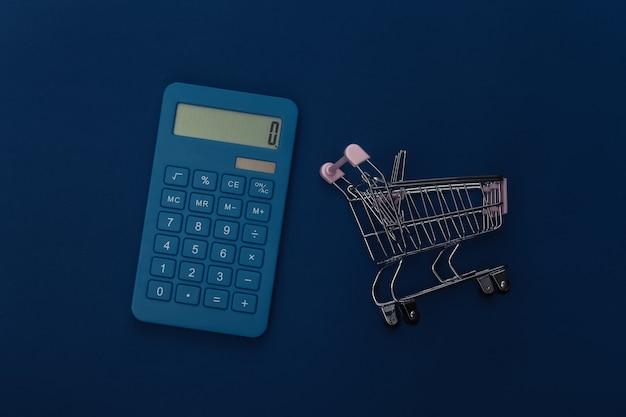 Carrinho de compras e calculadora em fundo azul clássico. custos de supermercado. cor 2020. vista superior.