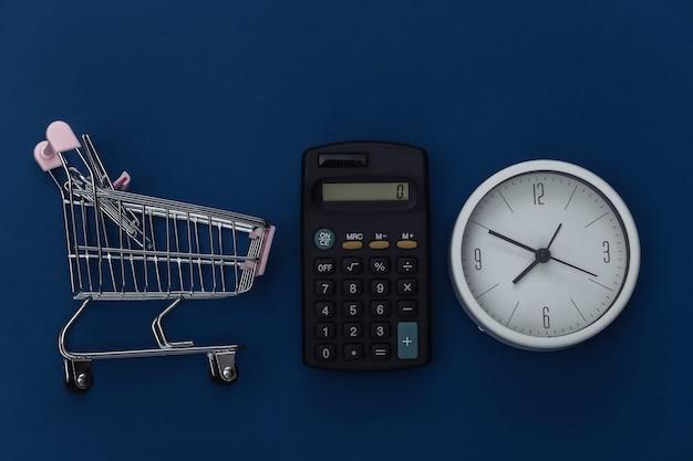 Carrinho de compras e calculadora, relógio no fundo azul clássico. custos de supermercado. cor 2020. vista superior.